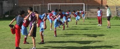 A Projects Abroad volunteer teaching sports in Peru leads children in a warm up stretch